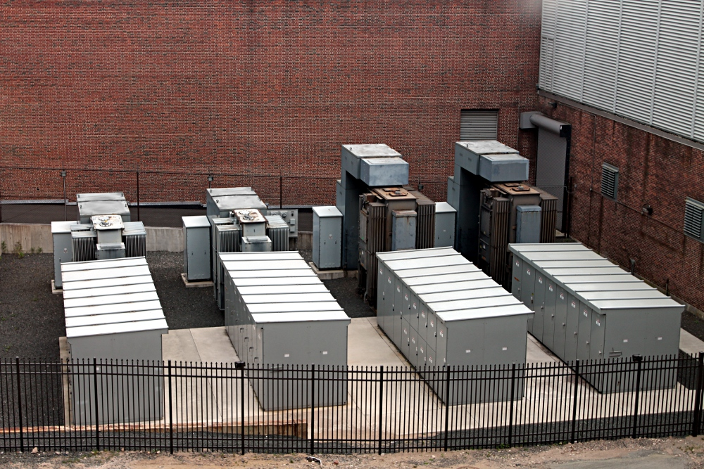 Image of an electrical switchyard set against a brick building.